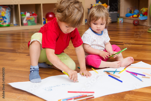 children draw together on a large sheet of paper in  room at home. Top view. Cute children having Fun Concept..