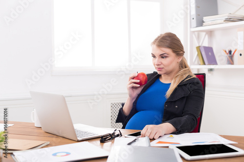 Pregnant woman eating apple in office copy space