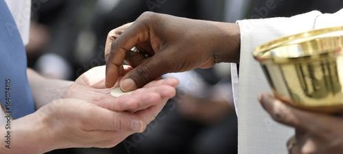 Dunkelhäutiger Priester gibt Hostie Heilige Kommunion Gottesdienst