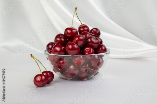 glass vase with big red cherries on a white background