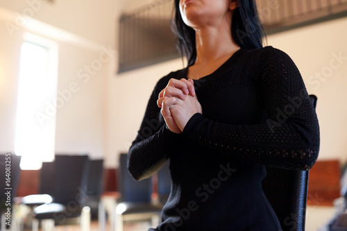 Poster close up of sad woman praying god in church