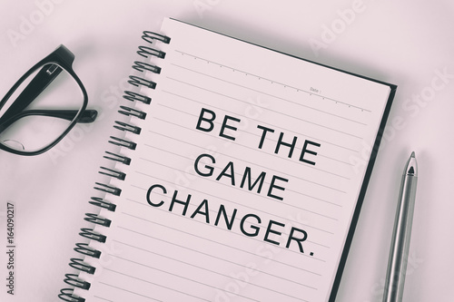 Inspirational quote - be the game changer: written on a note pad with eyeglasses and pen Plakat