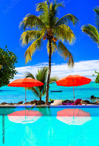 Tropical vacation - bar with turquoise swim pool and sea view. Mauritius island