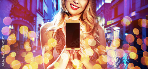 Fashion style portrait of a woman holding an electronic device