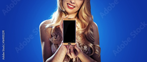 Fashion style photo of a blonde holding a smartphone