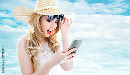 Closeup portrait of a young blonde using a smartphone