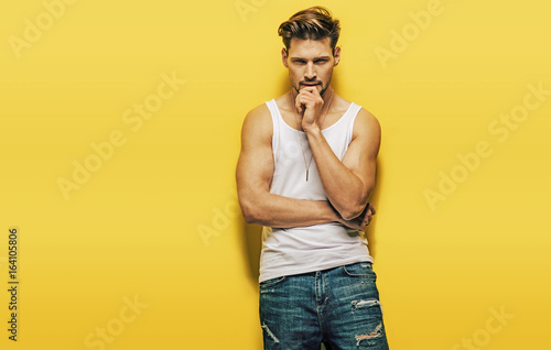 Foto op Plexiglas Artist KB Handsome, muscular man posing on a yellow background