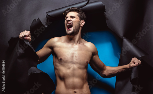Furious young man tearing up the background