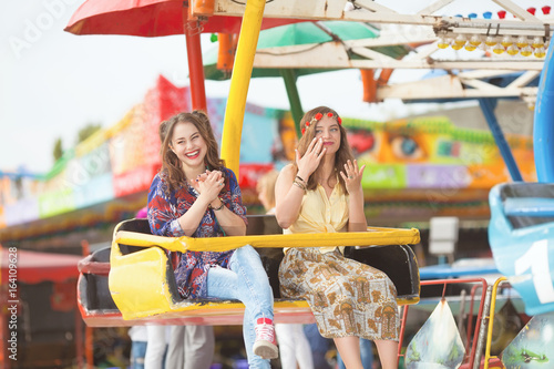 Two cheerful young girls are enjoying their ride at the amusement park
