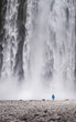 A man standing in front of the Skogafoss waterfalls in Iceland