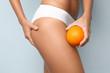 Leinwanddruck Bild - Young woman holding orange on light background. Cellulite problem concept