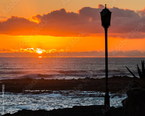 Ocean and orange cloudy sky in Fuerteventura at sunset with silhouette of a street lamppost in the foreground