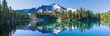 Wulkaniczna góra w porannym świetle odbijającym w spokojnych wodach jeziora.