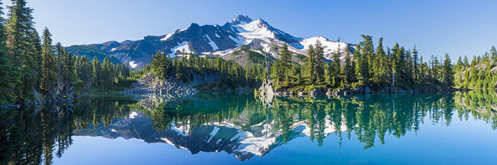 Volcanic mountain in morning light reflected in calm waters of lake. ©  Tom Fenske