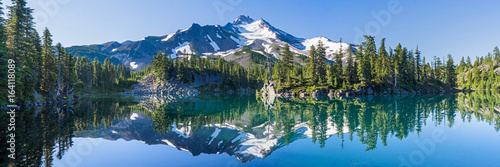 Volcanic mountain in morning light reflected in calm waters of lake. - 164118089