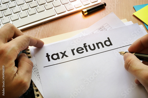 Hands holding documents with title tax refund.