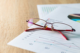 Close up  summary report and eyeglasses on table office. Concept of Data Analysis, Investment Planning, Business Analytics. - 164151058