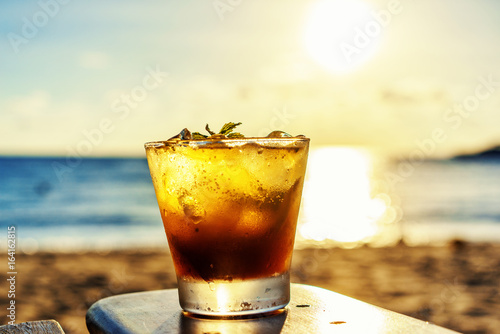The frozen glass of Mojito drinks on the beach at sunset with blur background.