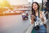 Fototapety Woman walking in bangkok city using phone app