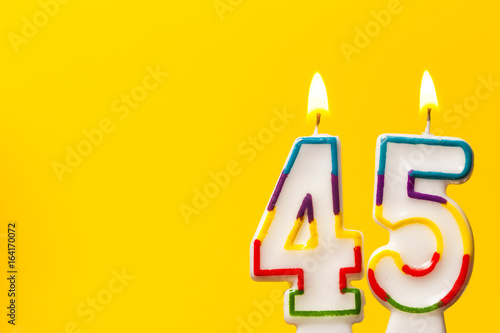 Number 45 birthday celebration candle against a bright yellow background Poster