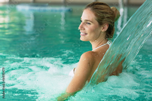Beautiful attractive woman enjoying time in pool - 164192479