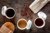 Coffee take out. Coffee cups with covers, coffee beans and cookies on wooden table backound top view