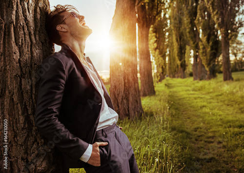Calm, relaxed man leaning on the tree