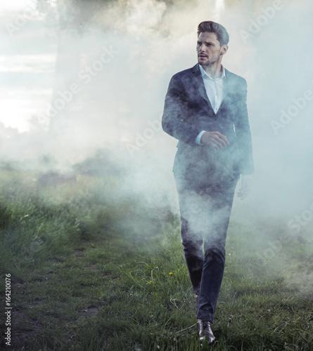 elegant young man walking in the morning haze