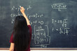 Beautiful Asian student writing on blackboard with chalk in classroom.