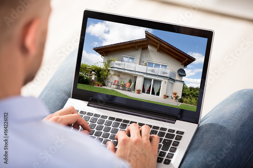 Man Looking At House Exterior On Laptop - 164226012