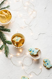 Whimsical holiday scene. Homemade T-Rex cookies with blue royal icing, coconut milk with cinnamon, Christmas tree twigs, and fairy lights. White texture background