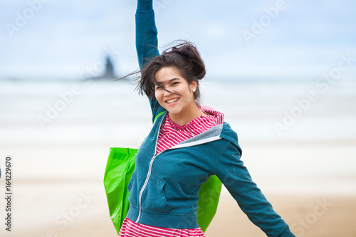 Plakát Happy teen girl in blue jacket  on beach, arms outstretched