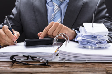 Businessman Calculating Invoice With Bill Stand On Documents