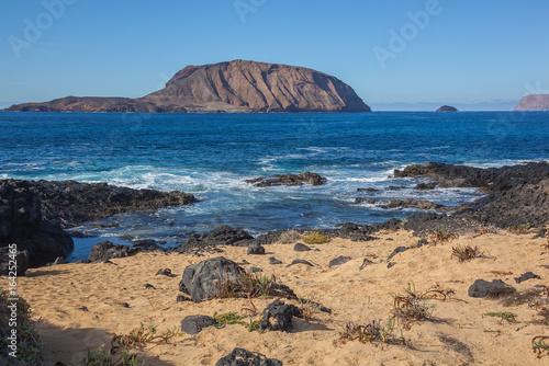 Foto op Plexiglas Canarische Eilanden Colorful sandy seacoast of Graciosa volcanic island with black lumps of lava, Lanzarote, Canary Islands, Spain