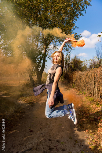 Plakát Happy girl laughs and works with the orange color of a smoke bomb in the forest