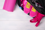 Fototapety Pink set in a sports bag on a gray board background