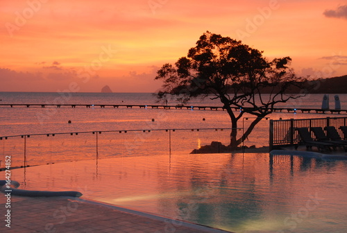 Foto op Canvas Koraal Couché de soleil avec piscine en Bord de Mer