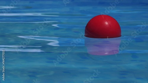 Red ball floating in clear blue swimming pool water, plaything in poolside for summertime activity and recreation