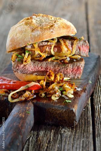 Gegrilltes Filetsteak vom Rind mit Röstzwiebel im reschen Brötchen serviert - Big meat sandwich: Grilled beef fillet steak with fried onion rings on a fresh roll