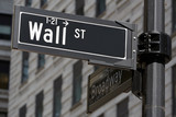 Wall Street and Broadway sign near Stock Exchange, financial district in New York in a sunny day