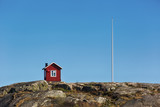 Small red wooden cabin on island in Sweden. - 164289288