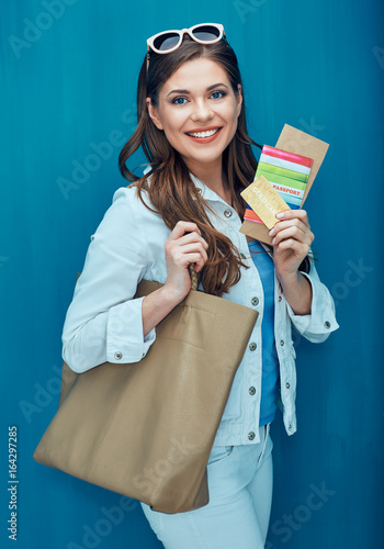 Travel concept portrait of smiling woman holding passport with ticket.