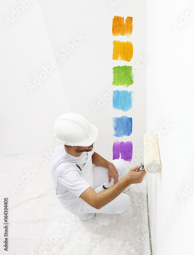 painter man with paint roller painting color samples, top from view isolated on blank white wall background