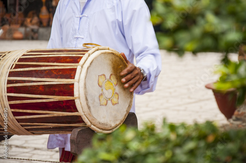 Vietnamese drum. The musician holds the drum and plays it Poster