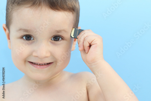 niño pequeño con tarjeta de memoria almacenando recuerdos