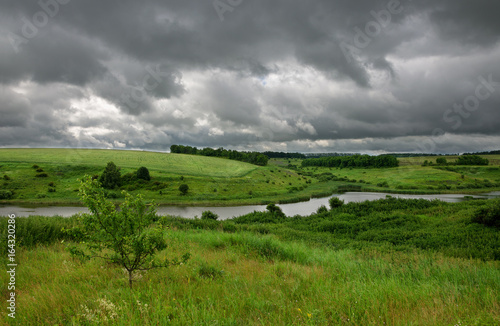 Cloudy summer scene with small river. Dramatic sky over the fields