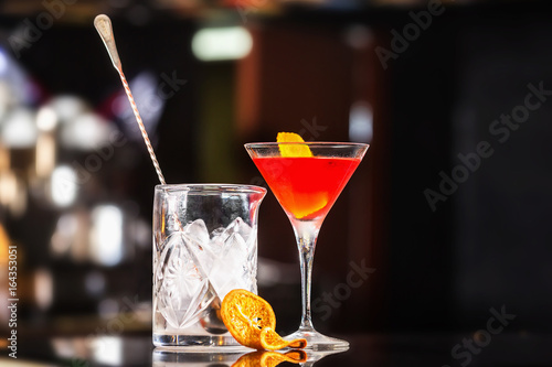 Closeup glass of Manhattan cocktail decorated with orange and decanter with ice at bar counter background Poster