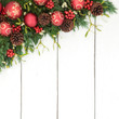 Christmas background border with bauble decorations, holly, mistletoe, ivy, fir and pine cones on rustic white wood background.