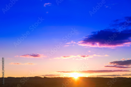 Landscape and dramatic sunset or sunrise sky. Summer or spring meadow nature