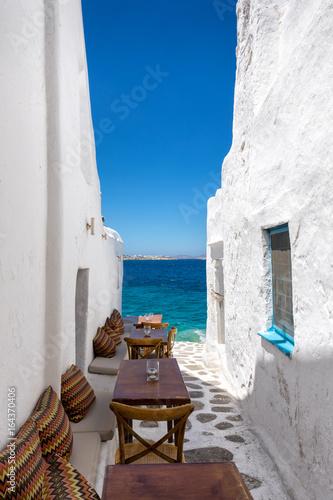 Tische und Stühle in einer Gasse am Meer in Mykonos, Kykladen, Griechenland